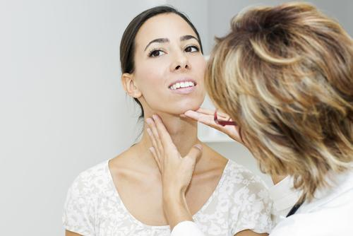 Doctor examining female patient's thyroid