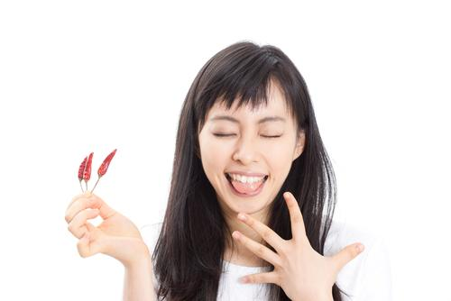 Womn sticking tongue out while holding red chili peppers