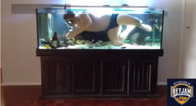 Guy necks a beer in his fish tank