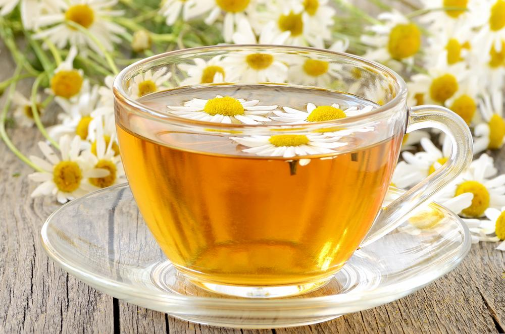 Herbal chamomile tea with chamomile flowers on wooden table