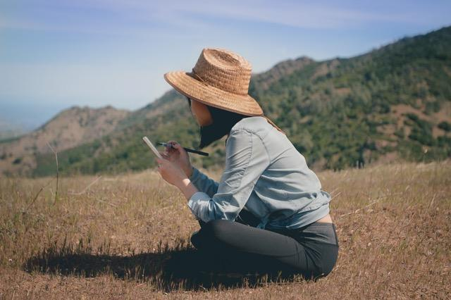Woman writing in field