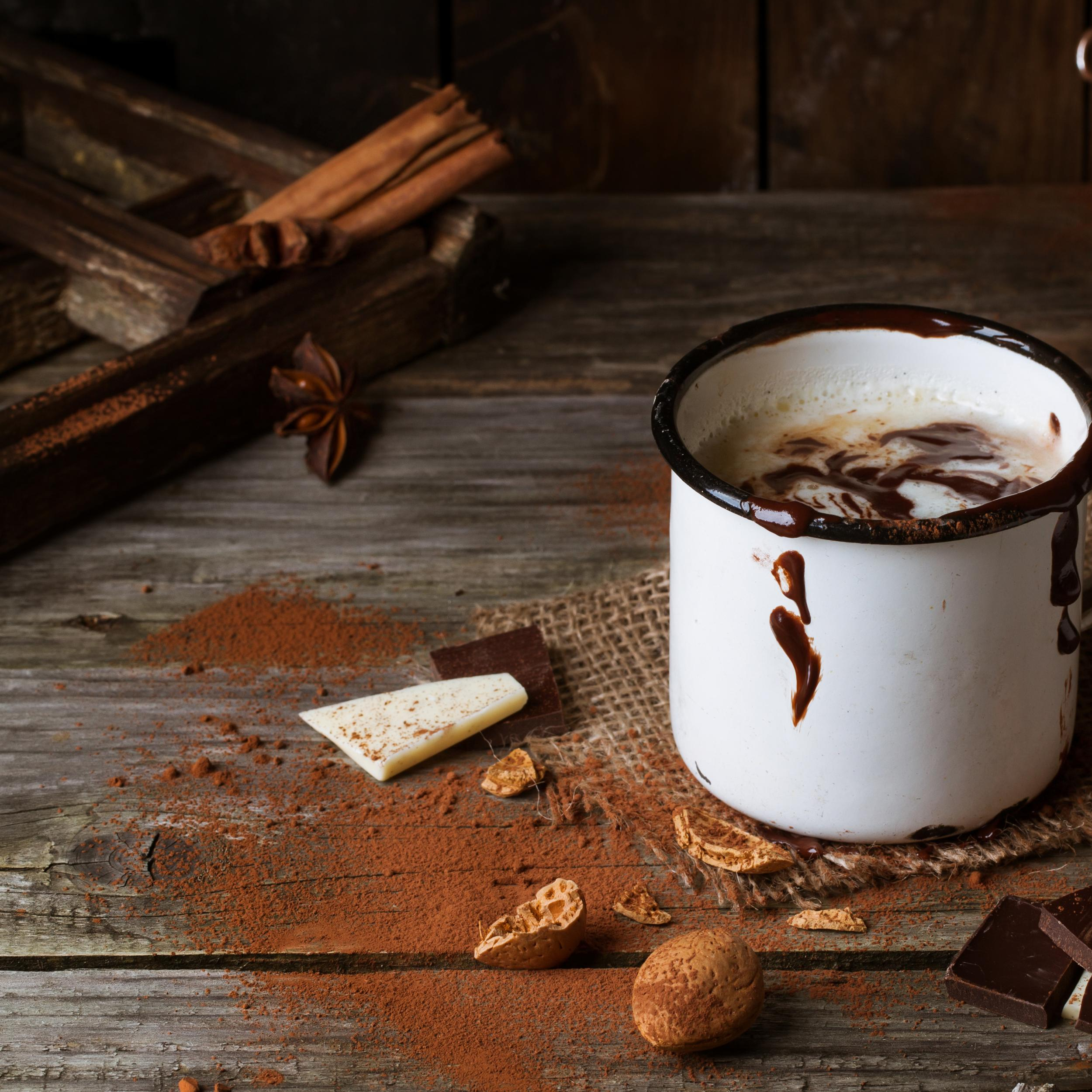 Mug with hot chocolate served with chunks of white and dark chocolate and almonds on old wooden table