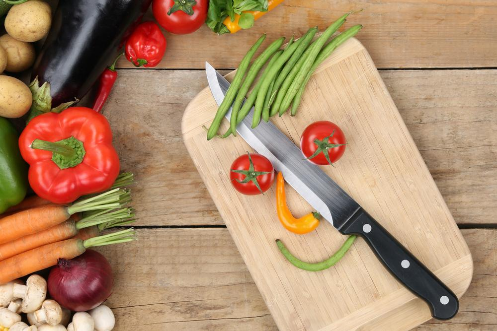 Preparing food smiling vegetables face on cutting board with knife