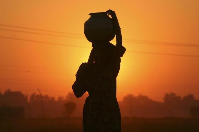A Gujjar or nomad woman carrying a pitcher filled with drinking water is silhouetted against the setting sun on the outskirts of Jammu December 3, 2011.