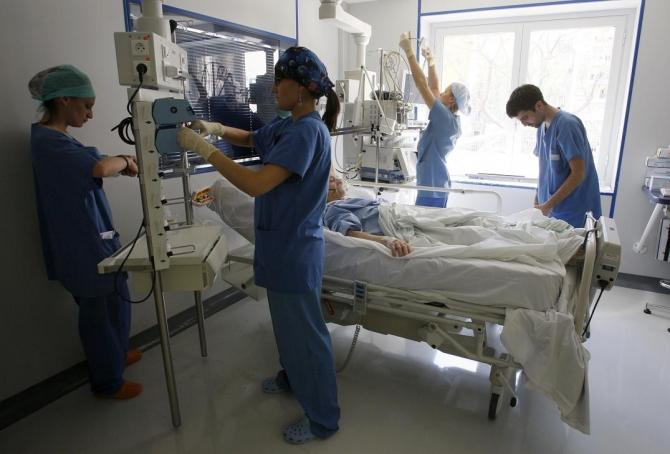 Nurses check a patient in the intensive care unit at the Ambroise Pare hospital in Marseille, southern France, April 8, 2008.