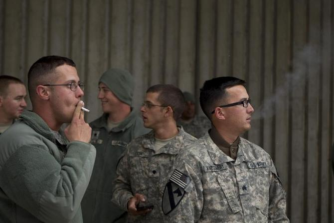 Soldiers from the 3rd Brigade, 1st Cavalry Division smoke cigarettes outside an airport in Bangor, Maine December 21, 2011 during a layover on a flight from Kuwait that will take the unit back to Fort Hood in the United States.