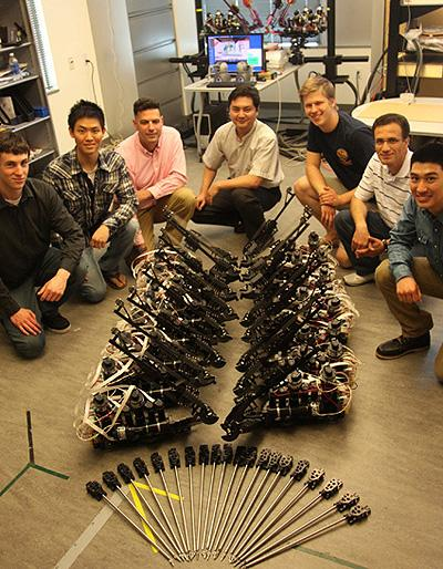 Team members posed with components of the Raven II surgical robotic systems developed in the Bionics Lab at the Baskin School of Engineering