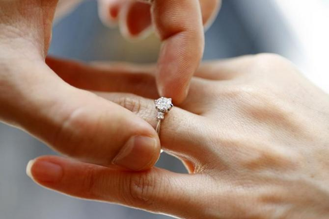 A man puts an engagement ring on a woman's finger during a photo opportunity at a jewellery store in Tokyo June 2, 2009.