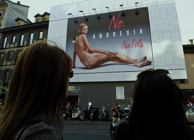 Two women look at an advertising board showing a shockingly emaciated naked woman in Milan September 24, 2007.