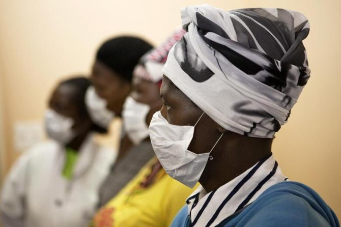 Patients with HIV and tuberculosis (TB) wear masks while awaiting consultation at a clinic in Cape Town's Khayelitsha township, in South Africa February 23, 2010.