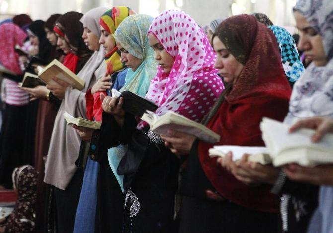 Muslim women hold the Koran as they perform the night prayer at a mosque during the holy month of Ramadan in Cairo