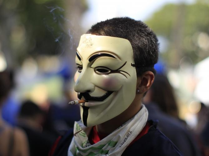A protester wearing a Guy Fawkes mask, smokes a cigarette during an Occupy LA protest in Los Angeles