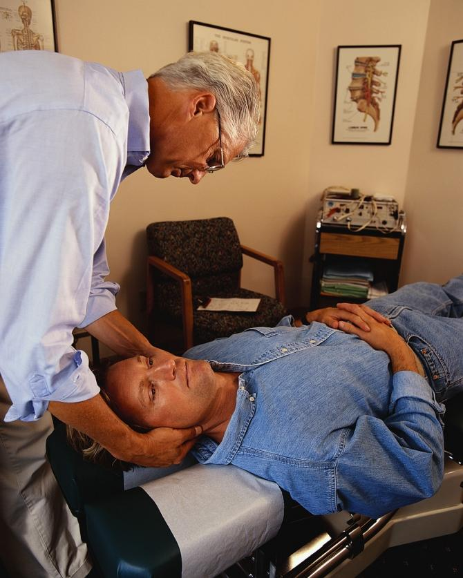 Chiropractor giving an adjustment to a male patient.