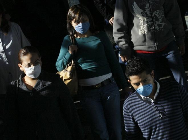 Passengers wear protective masks as they enter Chabacano subway station in Mexico City in April 2009