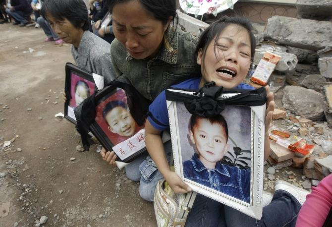 Researchers found that there was a 133 percent increase in the risk of a mother dying within the first two years of the death of a son or daughter. A woman holding a portrait of her 12-year-old son Feng Junwei cries next to the ruins of destroyed Fuxing p