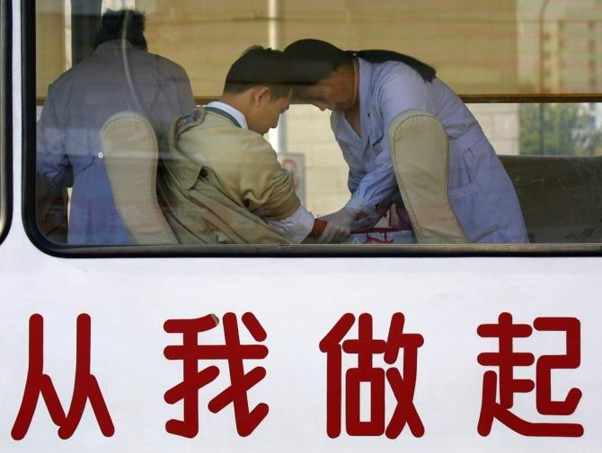 "A Chinese man donates blood at a government-run mobile donation centre decorated with Chinese characters which read ""Start From Me"" in Beijing November 18, 2001."