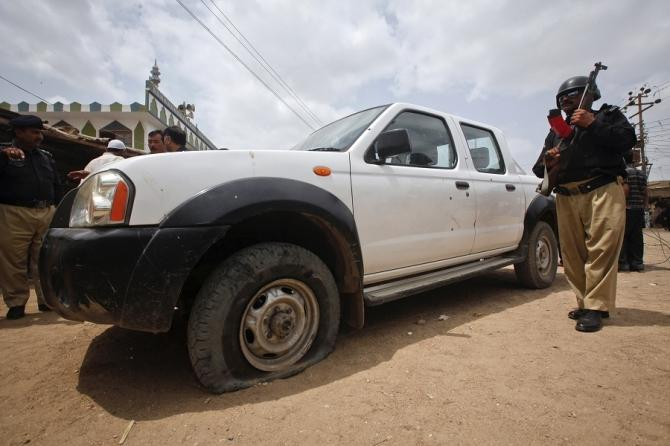 A policeman stands guard near a vehicle that was attacked by unidentified gunmen in Gadap Town, Karachi July 17, 2012. Gunmen in Pakistan shot and wounded a staff member of the World Health Organization (WHO) and an expatriate consultant working for the U
