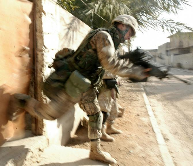 A U.S. Marine with Company, kicks in a door in the war torn Iraqi city of Falluja November 10, 2004. Researchers said that that intentionally preventing sleep in the early aftermath of stress exposure may be effective in reducing traumatic stress because