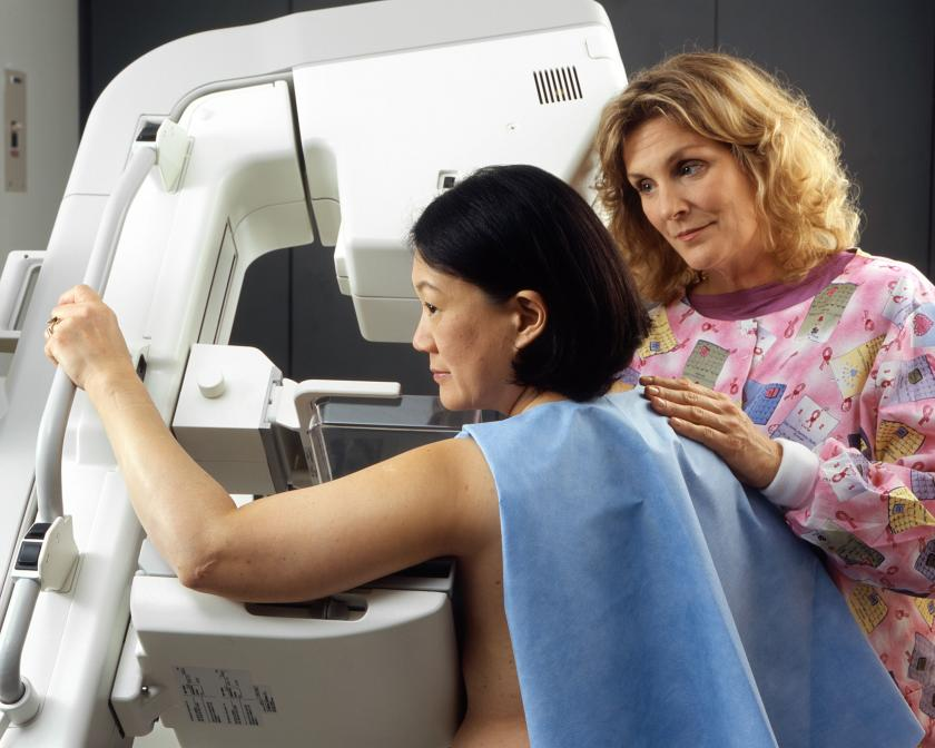 A technician positions a woman at an imaging machine to receive a mammogram