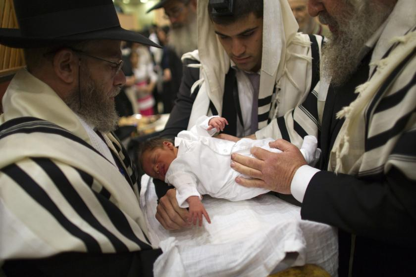 Ultra-Orthodox Jewish father holds his son before his circumcision.