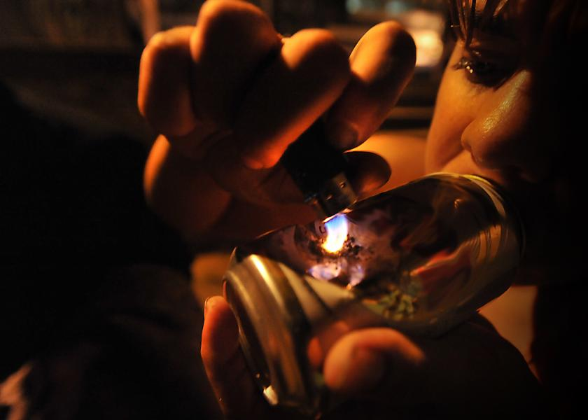 A woman smoking crack cocaine out of a can.