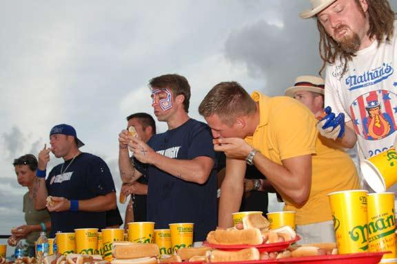 Men eating Nathan's hot dogs