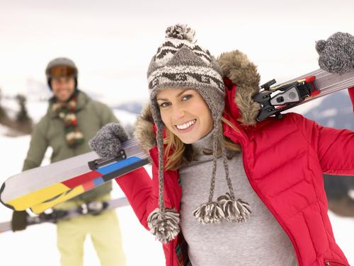 Woman holding skis on slope