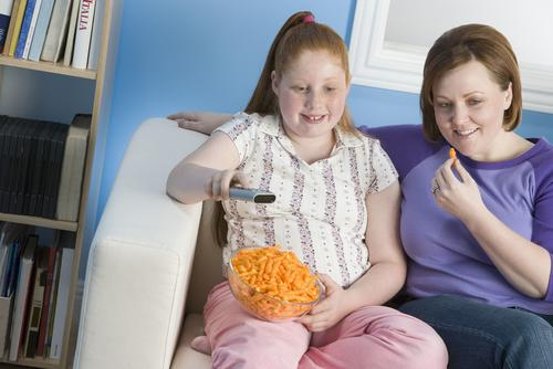 Mother and daughter watching TV with food