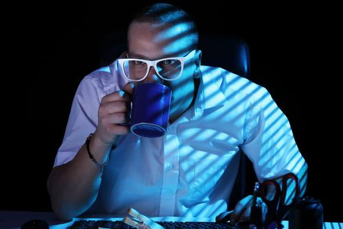 Night shift worker in front staring at computer screen while drinking coffee