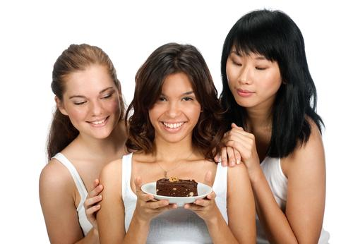 Woman holding a piece of cake with friends looking over her shoulder