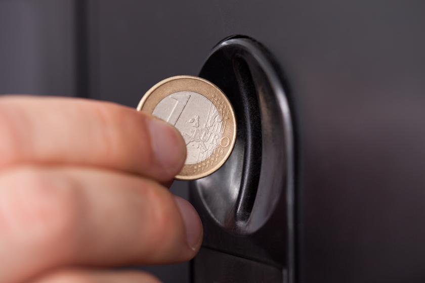 Hand inserting coin into vending machine
