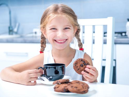 Little girl eating cookies and having tea in kitchen