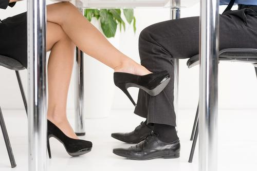 Woman's foot looking for man's foot under a business table