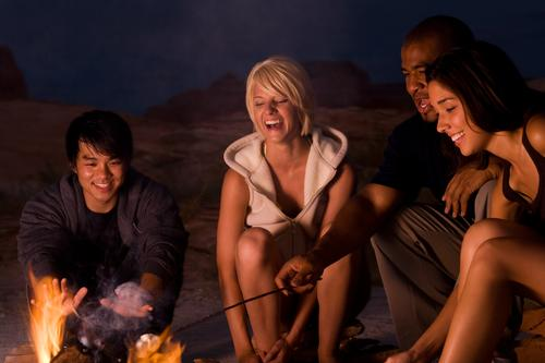 People sitting around a campfire at night roasting marshmallows