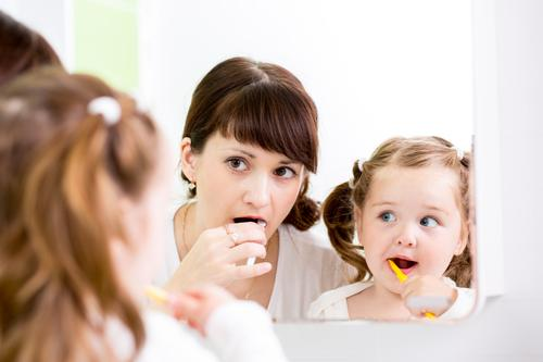 Mother teaching daughter how to brush teeth in front of mirror