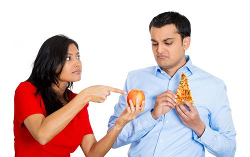 Woman convincing man to eat fruit instead of pizza