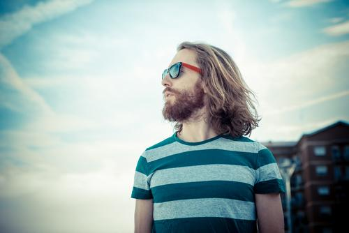 Hipster with sunglasses and beard outside in the sun