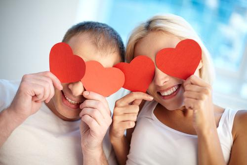 Happy couple holding paper hearts by their eyes