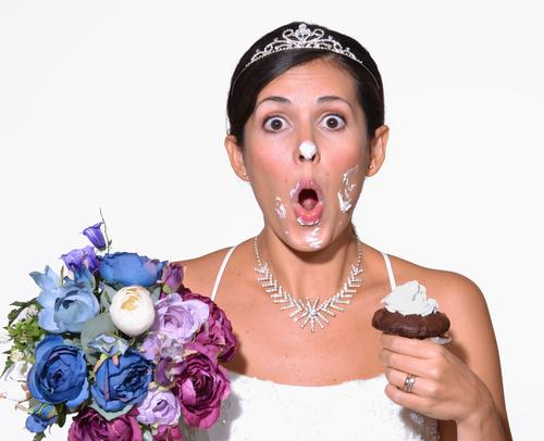 Bride with cake frosting all over her face