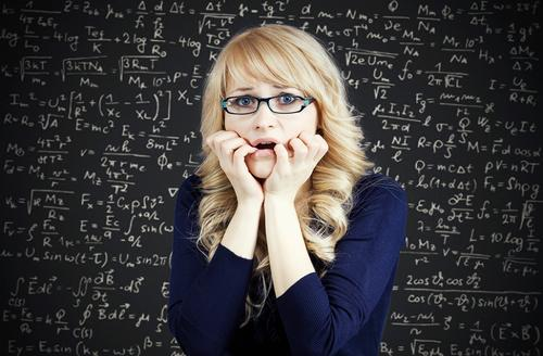 Woman feeling nervous and stressed in front of chalkboard with math problems