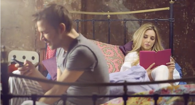 Couple in bed using electronic devices