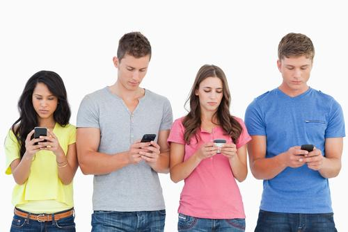 A group of people using their phones to send text messages