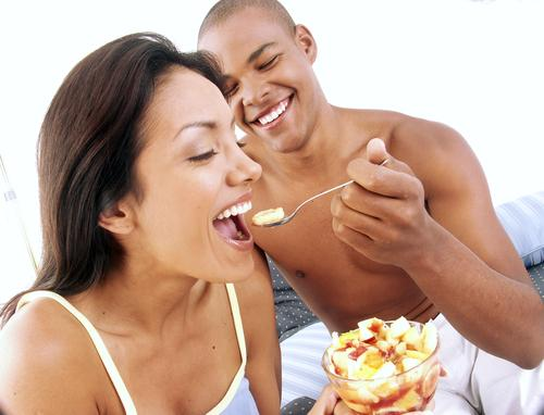 Young couple enjoying and eating fruit salad on bed