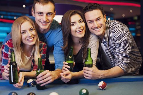 Friends drinking beers and playing pool