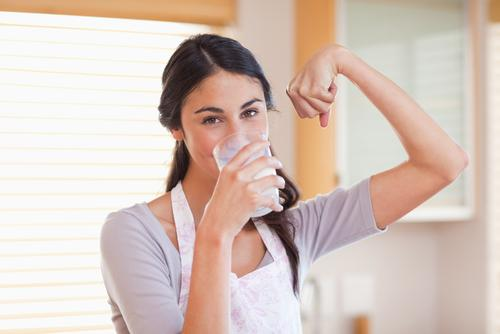 Woman drinking milk and flexing arm muscle