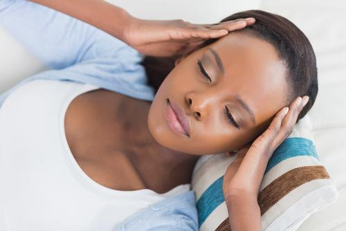 Woman lying on couch while having hands on head