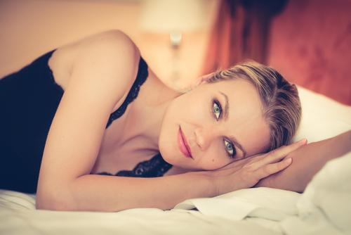 Woman relaxing on bed in hotel room
