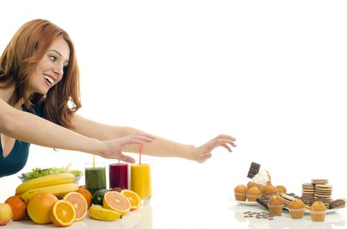 Woman choosing between healthy food and unhealthy food