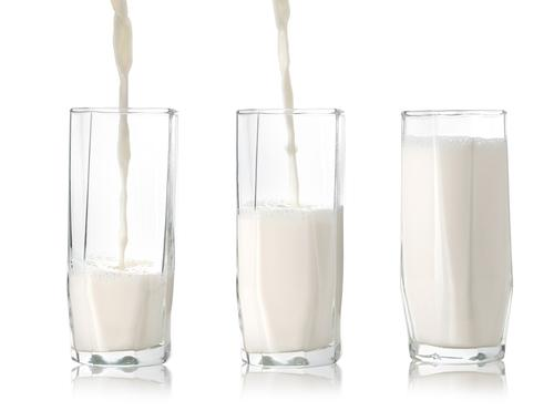 Three glasses of milk showing increasing amounts