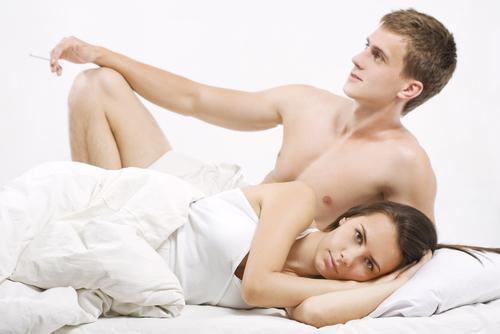 Young couple in bed looking different directions